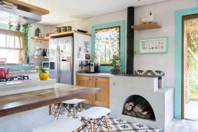 30. Área gourmet com fogão e lenha e mesa de madeira completa – Foto La de Casa