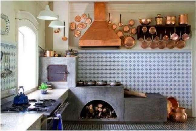 36. Área gourmet pequena com fogão a lenha e coifa metalizada em rose gold – Foto Pinterest