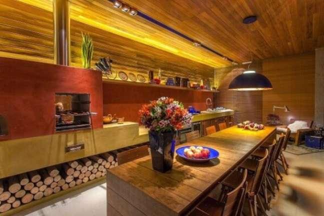 33. Área gourmet moderna com fogão a lenha e mesa de madeira grande -Foto Pinterest