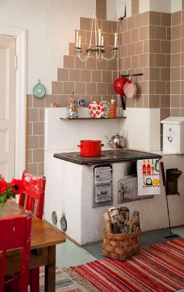 24. Área gourmet com fogão a lenha no canto da parede e mesa de madeira para servir as refeições – Foto Pinterest