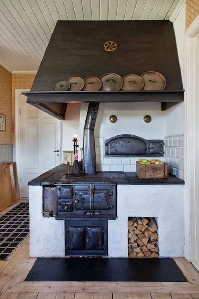 41. Decoração de área gourmet com fogão a lenha e coifa preta – Foto Pinterest