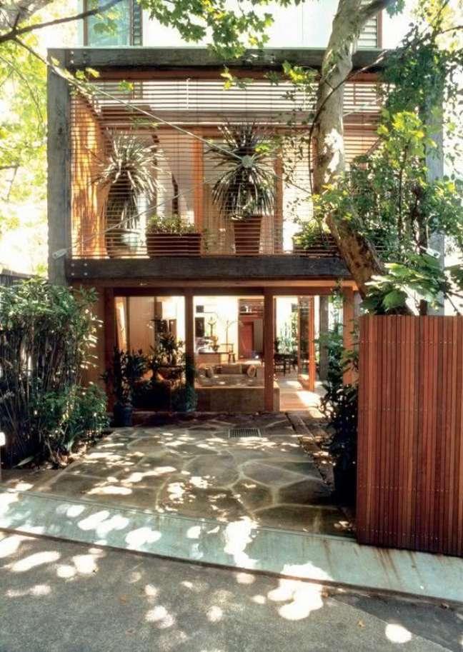 35. Modelos de garagem com portão de madeira e plantas na decoração – Foto Pinterest