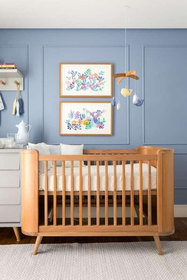 15. Quarto de bebê moderno com parede azul e berço de madeira – Foto Fashionismo