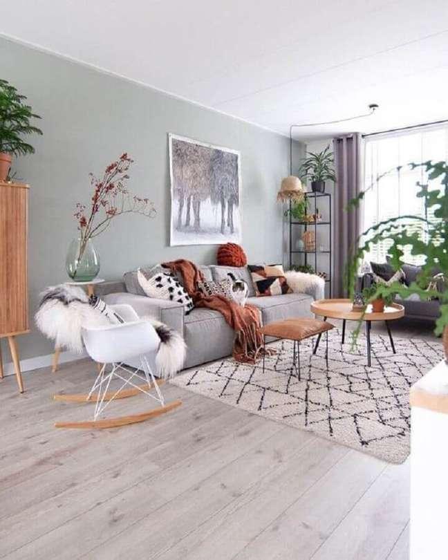 49. Sala de estar cinza e branco decorada com vasos de planta e cadeira eames de balanço – Foto: M-Habitat.fr