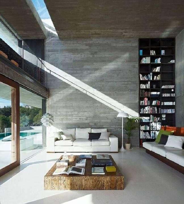 22. Decoração moderna para sala cinza e branco com mesa de centro rústica e estante para livros planejada – Foto: Architizer