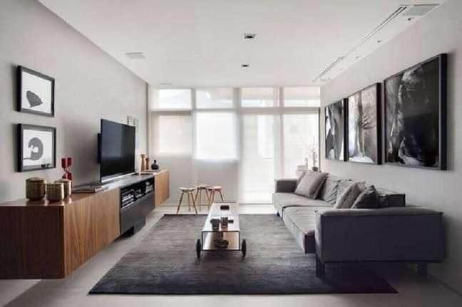 30. Decoração sala cinza e branco com rack de madeira e quadros grandes – Foto: Jeito de Casa
