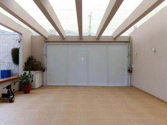 60. Piso cerâmica para garagem coberta na cor bege com portão branco – Foto Pinterest