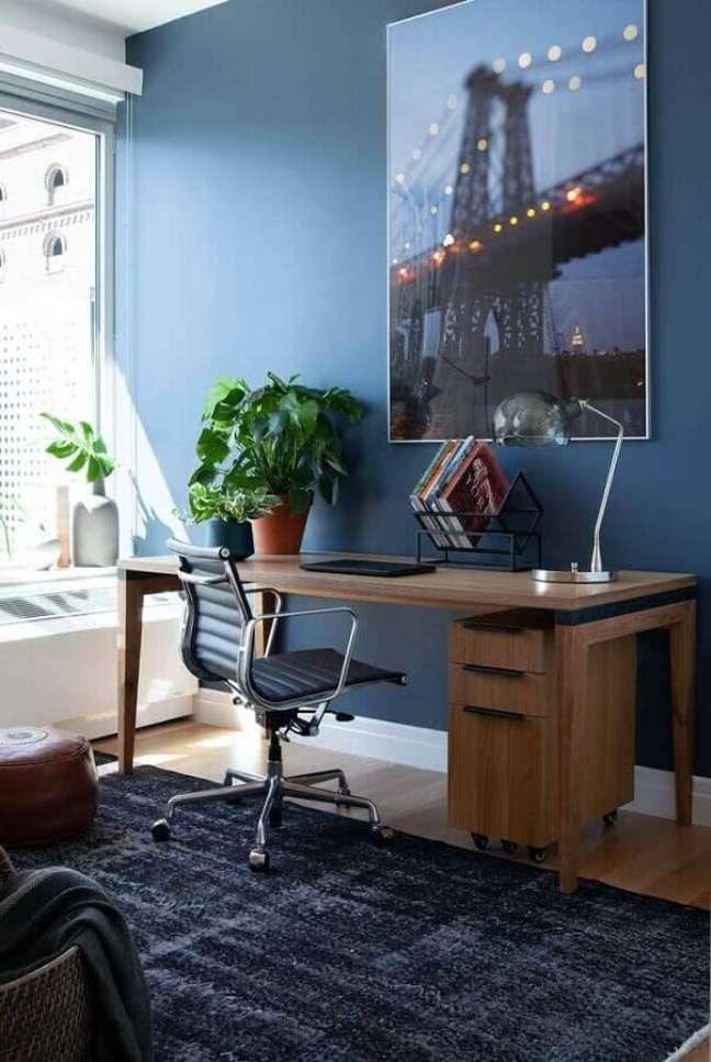 23. Decoração com quadro grande e escrivaninha home office azul – Foto: Architecture Art Designs