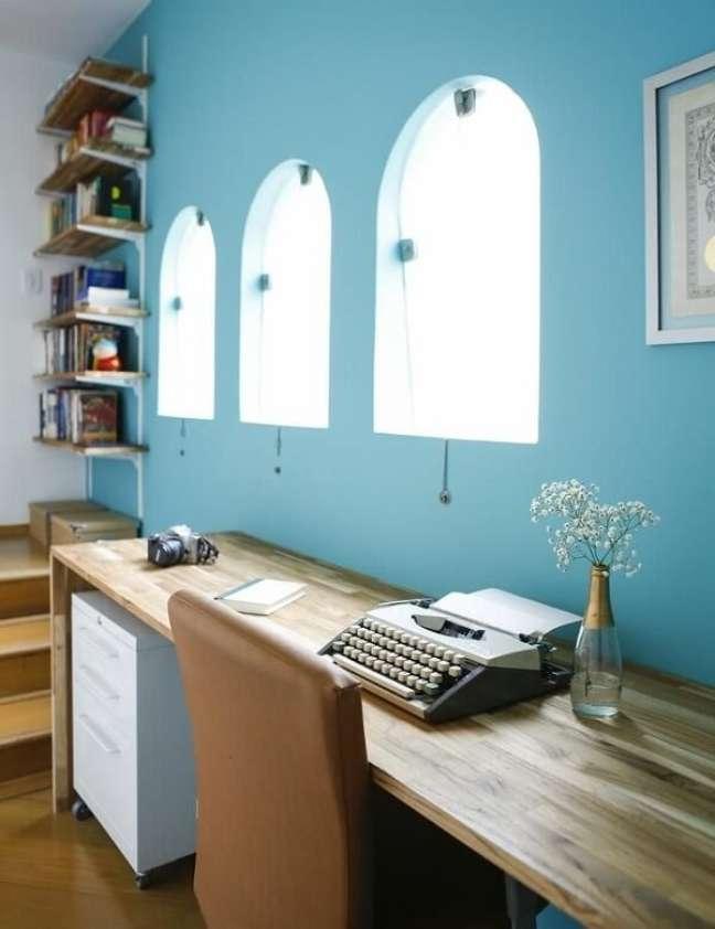 25. Home office com parede azul, escrivaninha de madeira e gaveteiro branco. Projeto de Buji Decoração Reuso