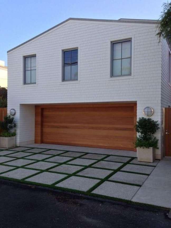 36. Cerâmica para garagem com portão de madeira e grama no piso – Foto Pinterst