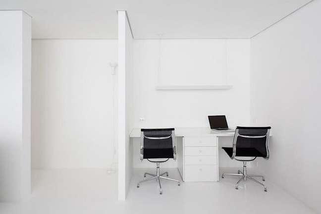 9. Escritório clean com cadeira preta e escrivaninha com gaveteiro branco. Projeto de Felipe Hess