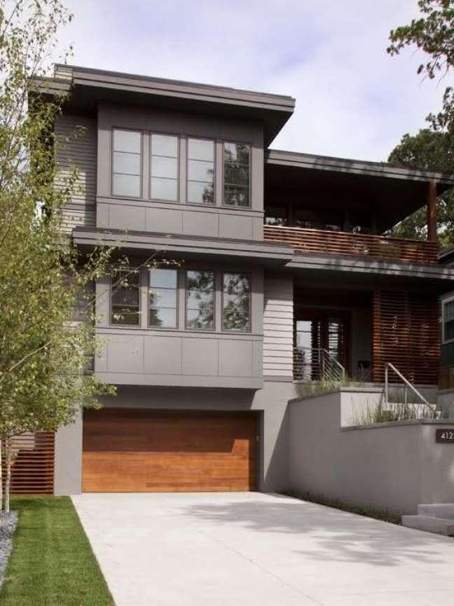 17. Casa grande com cerâmica para garagem cinza e portão de madeira – Foto Pinterest