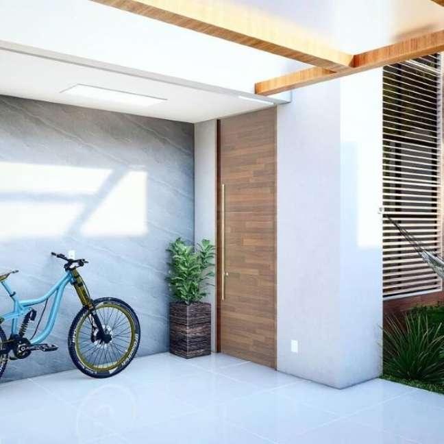 37. Cerâmica para garagem com portão de madeira moderno – Fonte Jordan Lima