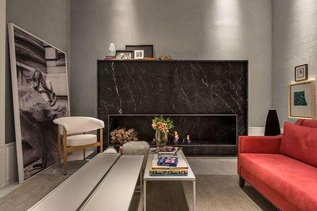 3. Sala de estar com lareira revestida com mármore preto e sofá vermelho luxuoso – Foto Lidia Maciel