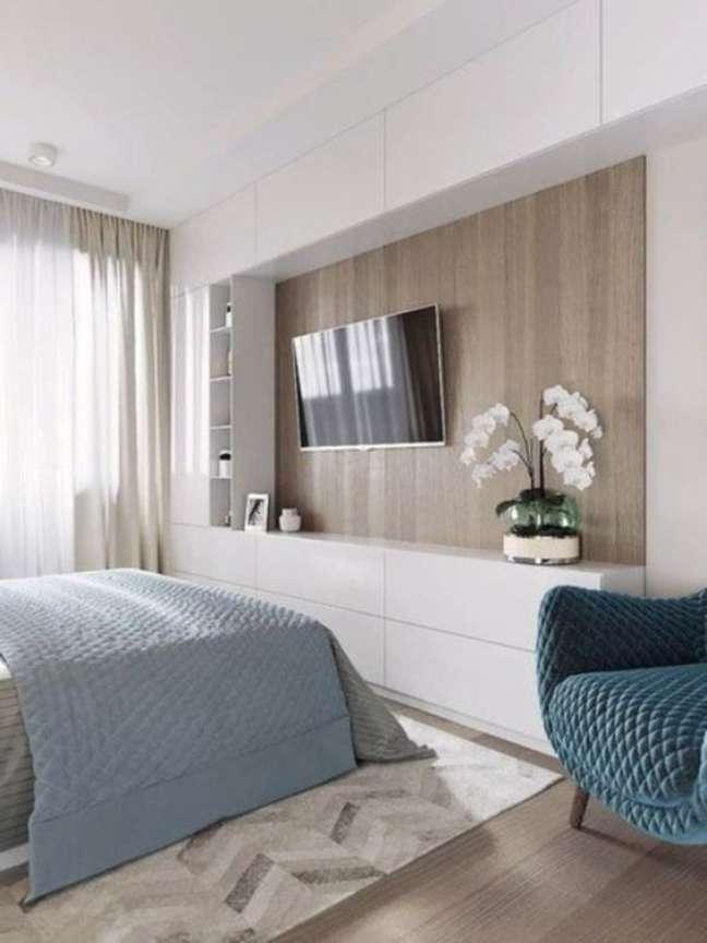 14. Rack para quarto branco com cama de casal e poltrona azul – Foto Pinterest