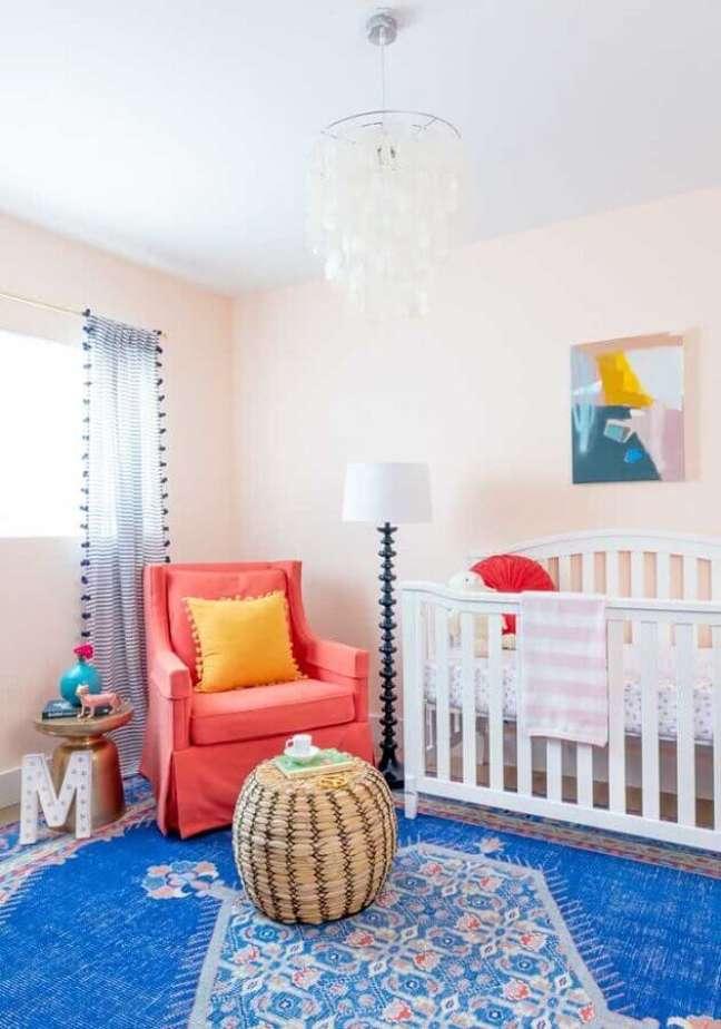 5. Decoração simples de quarto para bebê com tapete azul e poltrona rosa – Foto: Pinterest