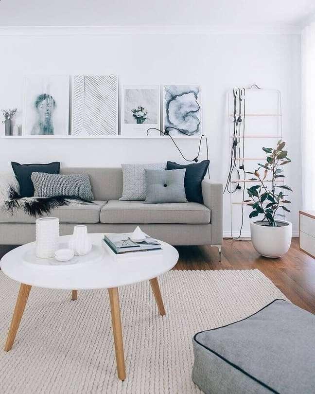 2. Decoração estilo escandinavo para sala cinza e branco com mesa de centro redonda e prateleiras para quadros – Foto: Pinterest