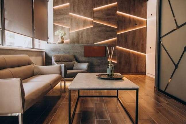 1. Decoração de sala moderna com luz de LED na parede amadeirada – Foto: Freepik