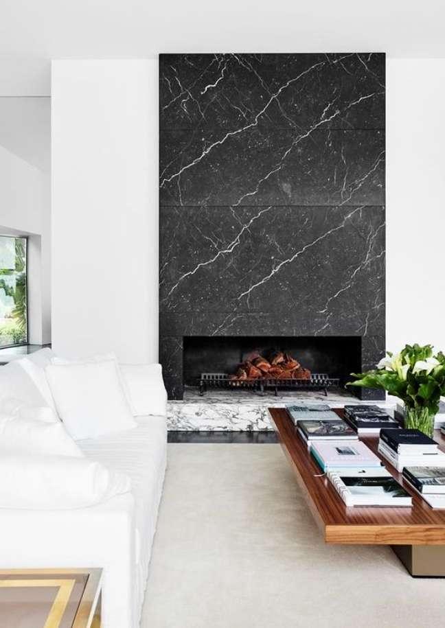 9. Lareira revestida com mármore preto na sala branca e chique – Foto Homes to Love