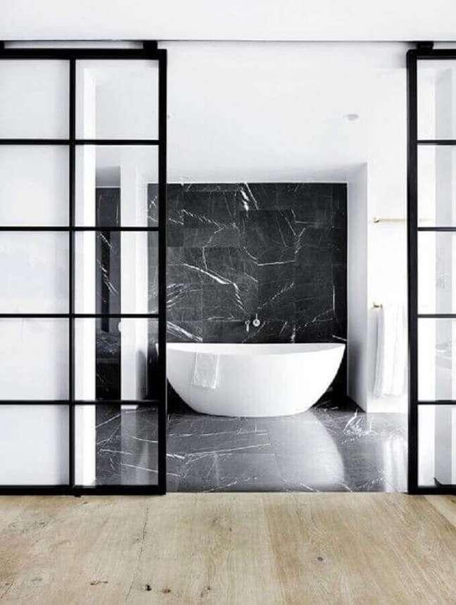 22. Banheiro moderno com revestimento de mármore preto e banheira branca – Foto Space Cph