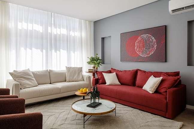 6. O sofá vermelho quebra a neutralidade e conversa diretamente com as poltronas e quadro. Foto: Dhani Borges