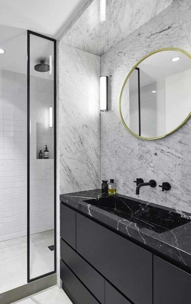 18. Banheiro sofisticado decorado com espelho redondo e bancada de mármore preto – Foto Behance