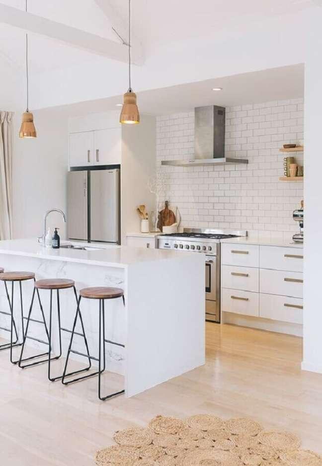 36. Decoração com armários brancos e ilha de cozinha com banqueta minimalista – Foto: Apartment Therapy