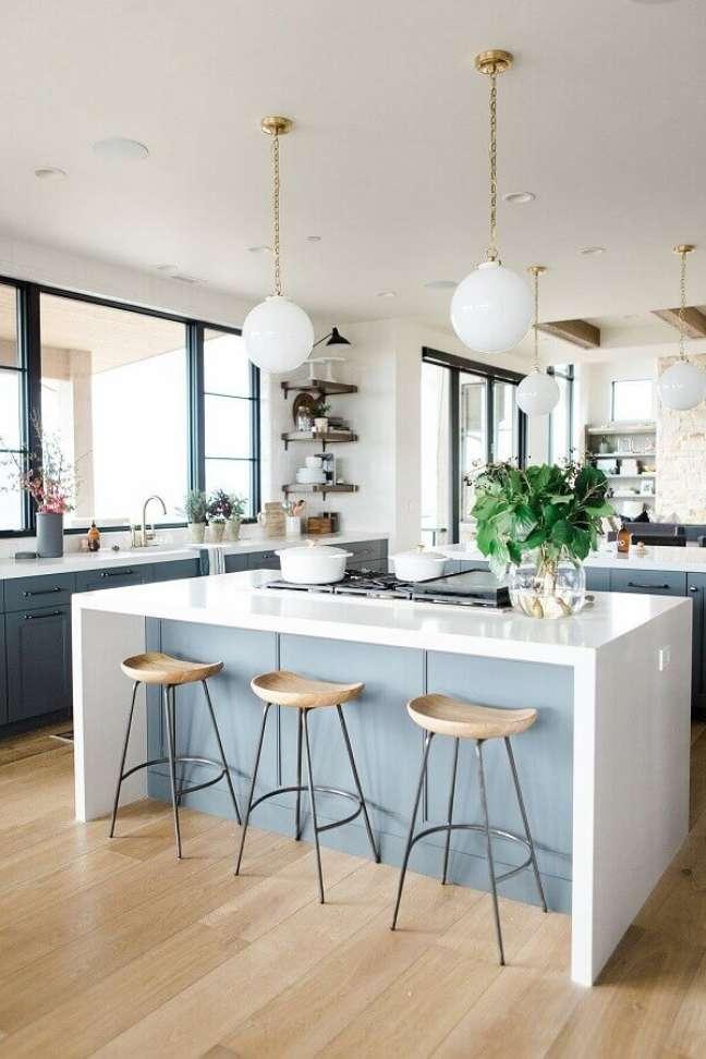 32. Decoração azul e branco com banqueta para ilha de cozinha grande – Foto: McGee & Co