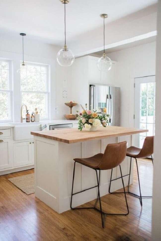 17. Banquetas estofadas para ilha de cozinha branca decorada com luminária de vidro – Foto: Arquitetas Express