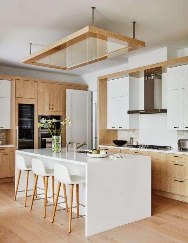 23. Cozinha branca com madeira decorada com banqueta alta para ilha – Foto: House & Home