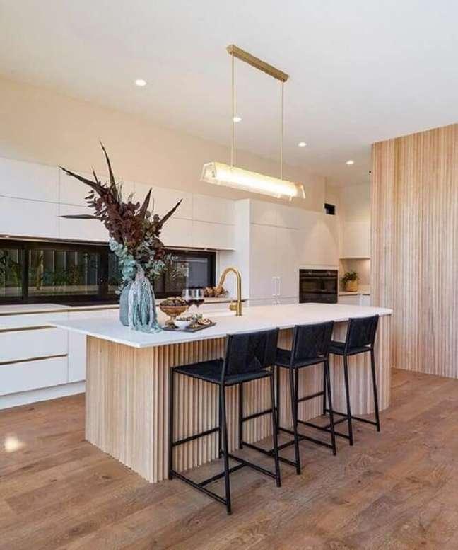 3. Cozinha amadeirada decorada com armários brancos e banqueta alta para ilha – Foto: Homes To Love