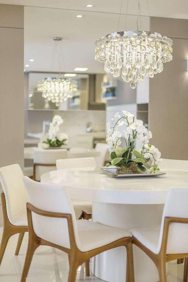 36. Mesa de jantar branca redonda com lustre de cristal e cadeiras brancas -Foto Homify