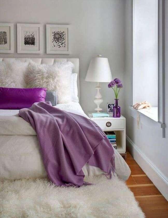 22. Quarto de casal com tapete de lã na ponta da cama e decoração em tons de roxo – Foto Planete Deco