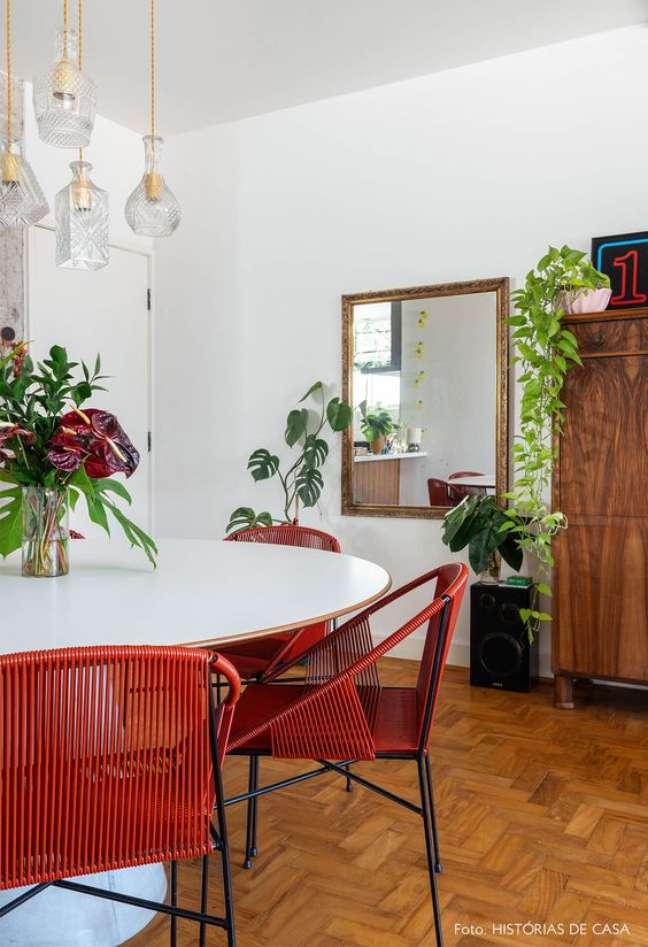 9. Mesa de jantar branca e redonda com cadeira vermelha – Foto Histórias de Casa