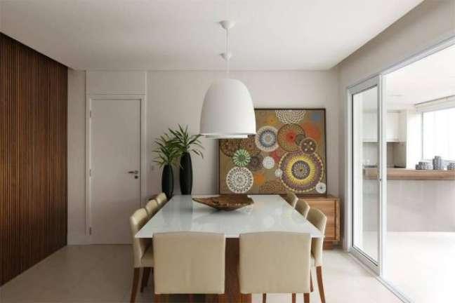 38. Mesa de jantar quadrada branca com cadeira bege e quadros geométricos – Foto Revista VD