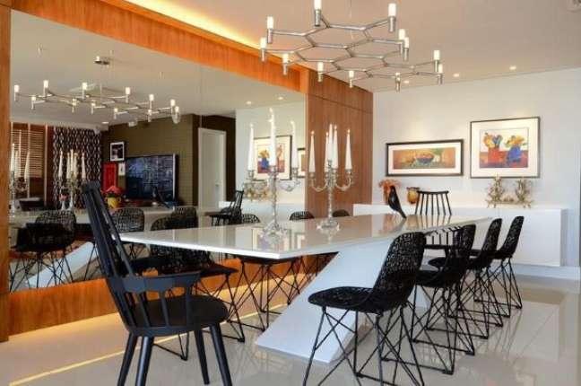 37. Mesa de jantar branco com cadeiras pretas lustre moderno e parede de espelho – Foto Rodrigo Maia
