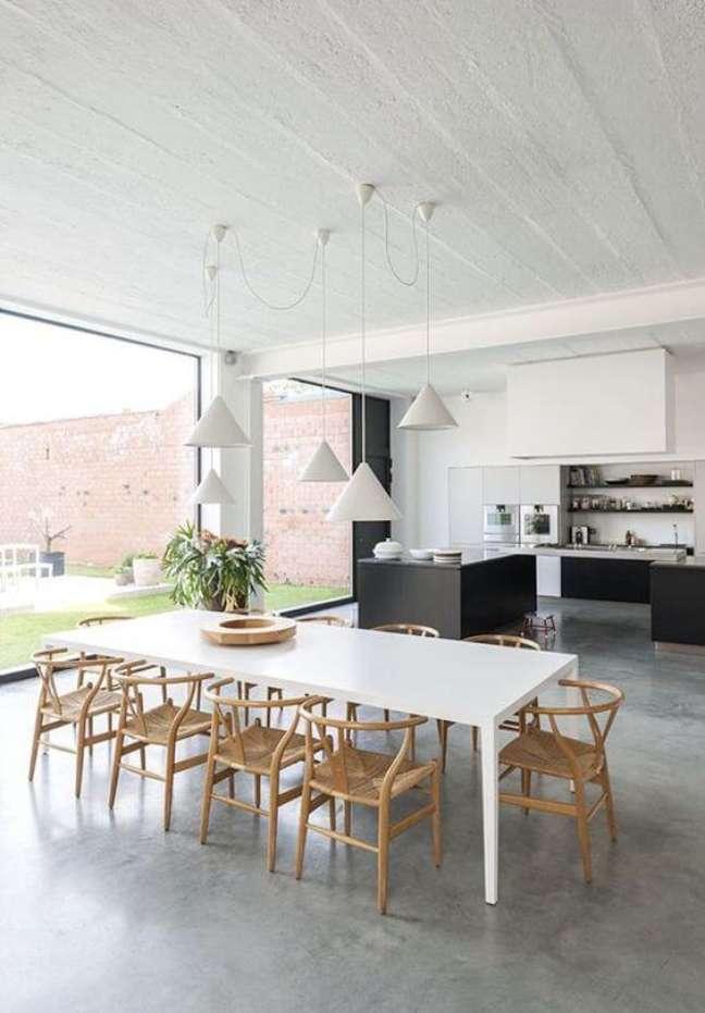 1. Mesa de jantar branca para varanda gourmet clean com piso de cimento queimado e cadeiras de madeira – Foto El Hombre