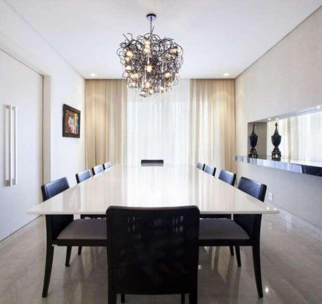 26. Mesa de jantar branca com cadeiras pretas e lustre moderno no centro -Foto charquitetura