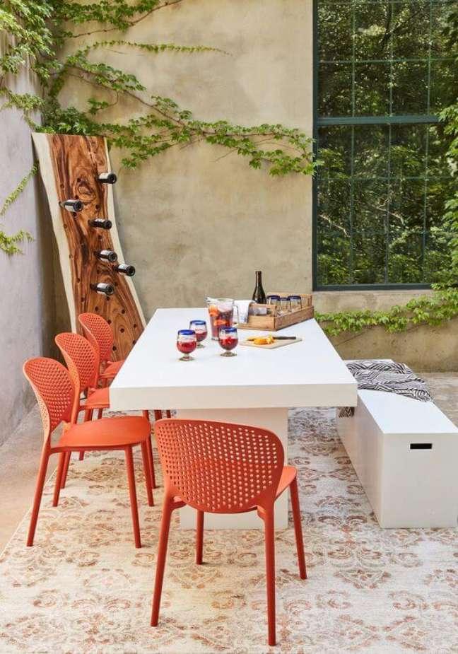 63. Cerâmica para área externa com mesa de jantar branca e cadeiras laranja -Foto Boxhill