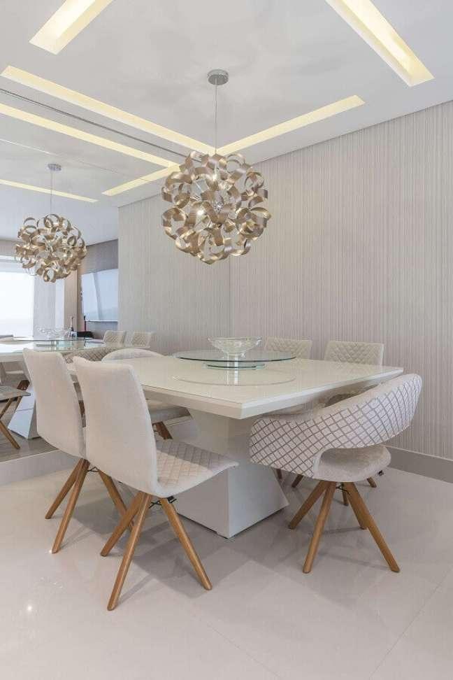 52. Sala moderna com mesa de jantar branca e cadeiras da mesma cor com iluminação de lustre redondo – Foto Pinterest