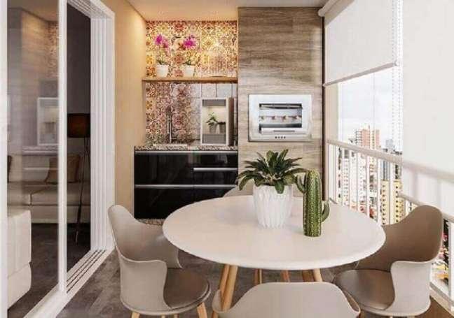 55. Varanda pequena com churrasqueira gourmet e mesa de jantar branca redonda para receber amigos – Foto Webcomunica