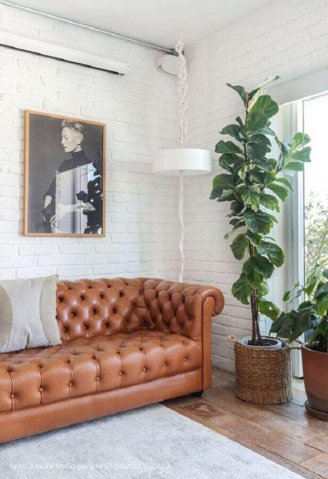 49. Sala simples decorada com vaso de chão e sofá cor caramelo com acabamento capitonê – Foto: Histórias de Casa
