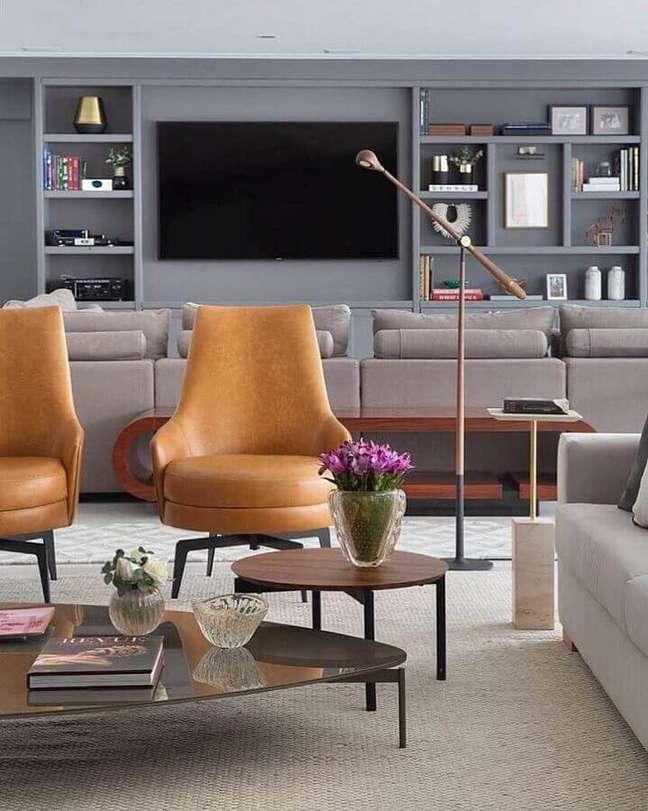 36. Sala cinza moderna decorada com poltrona cor caramelo e luminária de piso – Foto: éh!DECOR