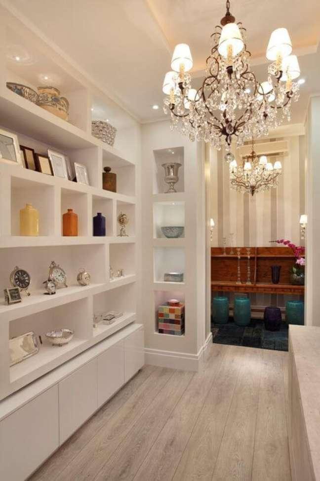 36. Estante de gesso branca para sala moderna com lustre de cristal – Foto Pinterest