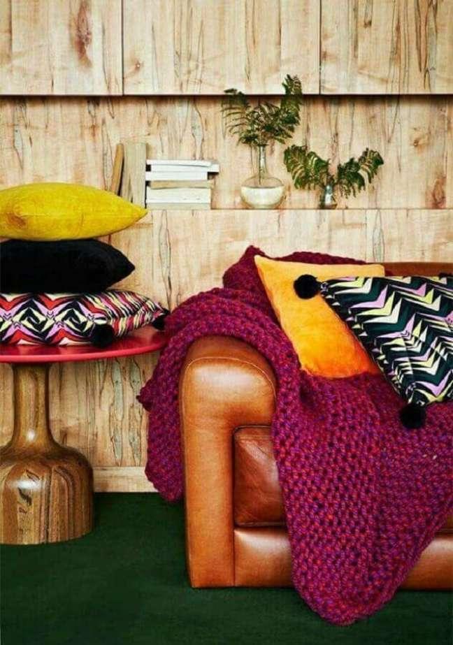 43. Sala decorada com parede rústica de madeira e sofá cor caramelo de couro – Foto: Pinterest