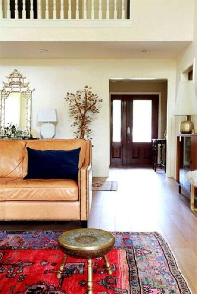 47. Sala simples decorada com sofá cor caramelo e tapete vermelho – Foto: Jeito de Casa