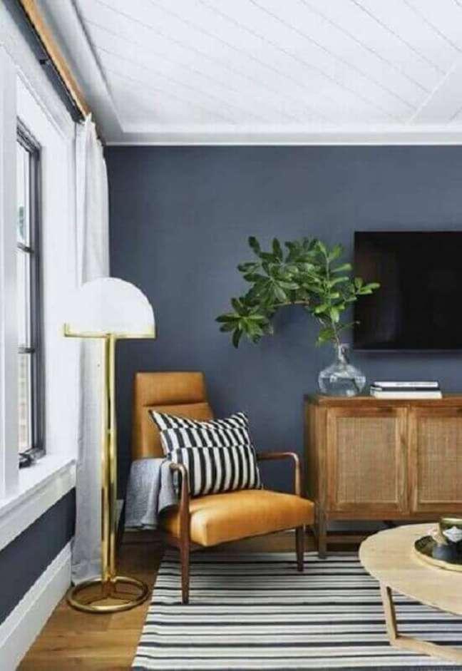 29. Poltrona de madeira com estofado cor caramelo para decoração de sala de TV cinza – Foto: Pinterest