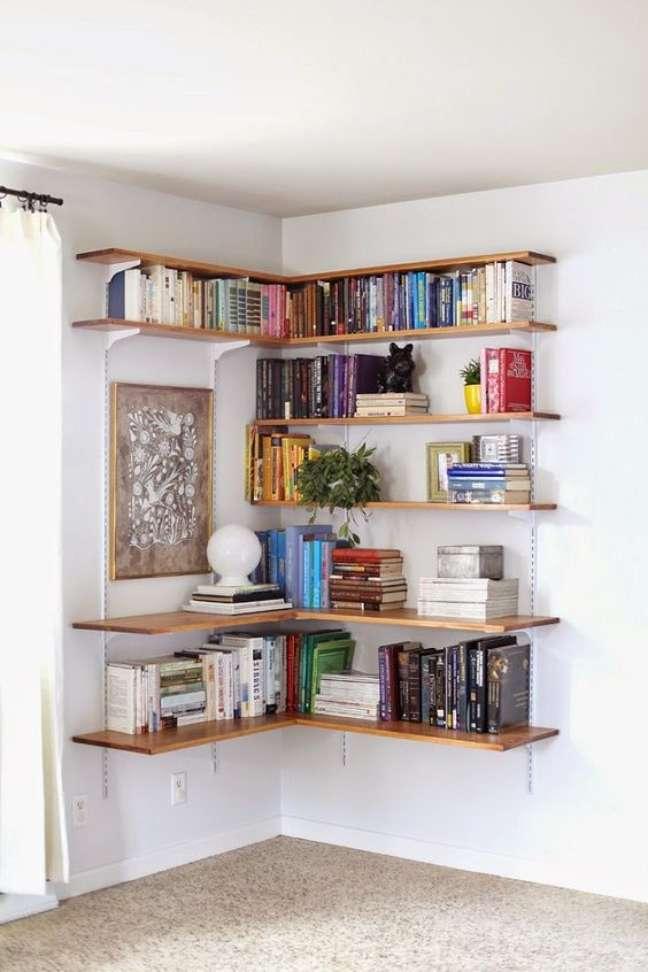 24. Estante de canto com prateleiras de madeira e livros variados – Foto Decoração e Invenção