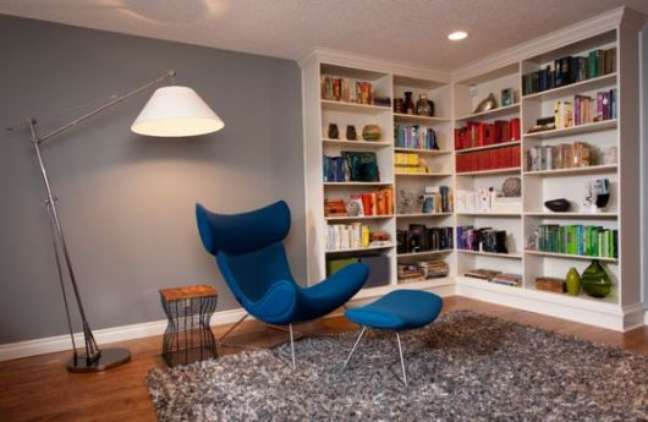 51. Sala de estar com estante de canto e poltrona azul – Foto Casa Construçõ