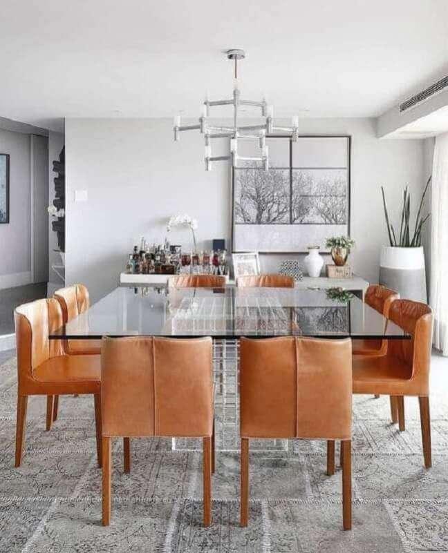 12. Cadeira cor caramelo para sala de jantar moderna decorada com mesa de vidro quadrado – Foto: Histórias de Casa
